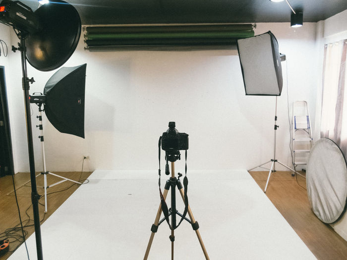 Tripod Camera And Lighting Equipment In Empty Studio