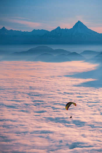 People flying over mountain against sky during sunset