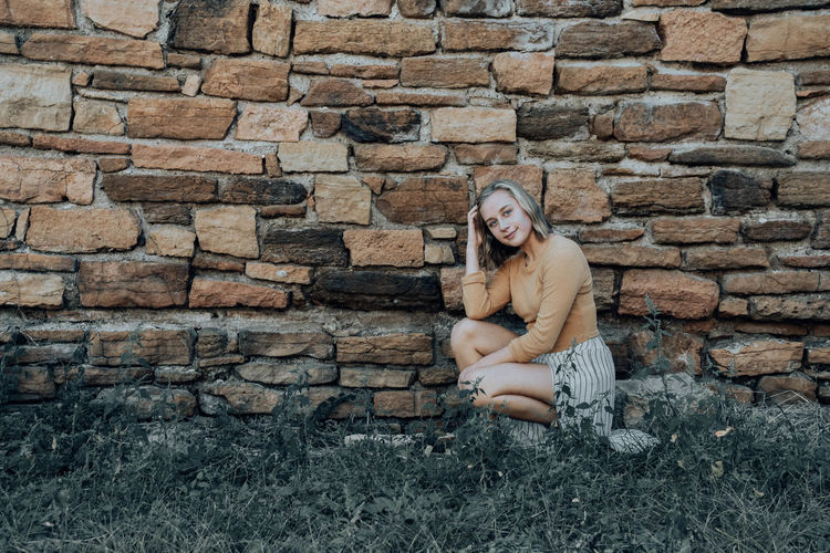 Full length portrait of woman sitting against brick wall