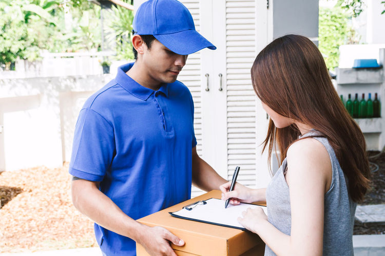 Woman putting signature in clipboard on cardboard box with delivery man Adult Business Casual Clothing Communication Day Females Holding Indoors  Lifestyles Men Occupation People Real People Receiving Signing Standing Two People Waist Up Women Young Adult Young Women