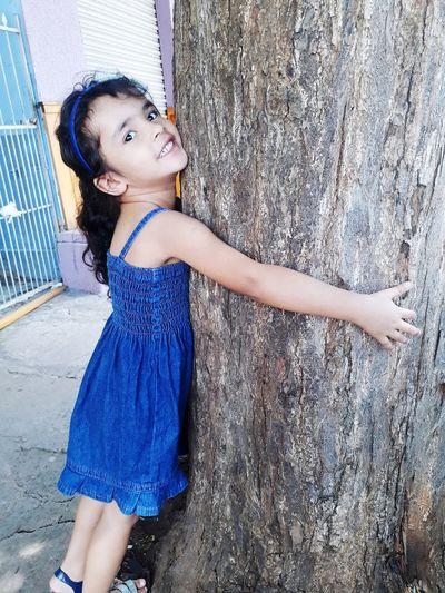 Portrait of cute girl embracing tree trunk