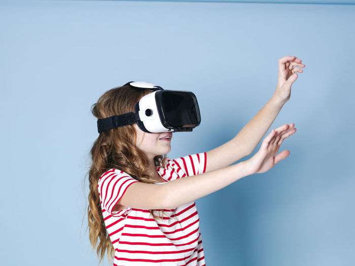 smiling positive girl wearing virtual reality glasses goggles headset, vr box. connection, modern, new generation, concept. girl trying to touch objects in virtual reality, studio shot on blue background Cyberspace Goggles Virtual Glasses Simulation Girl Entertainment Future Generation 360 3D Box Design Business Fun Joyful Gaming Game Electronic Futuristic Blue Copy Space Experience Young Human Woman Model Visual Viewer Video Film Look Observe Learn Pupil School Funny Technology Technical University  Visions Safety Glasses Glass Cool Female One Translated With Www.DeepL.com/Translator Virtual Reality Simulator Childhood Child Indoors  Women Girls Females Striped People Front View Studio Shot 3-d Glasses Leisure Activity Portrait Headshot Waist Up Human Arm Blue Background Hairstyle Arms Raised Innocence Human Limb