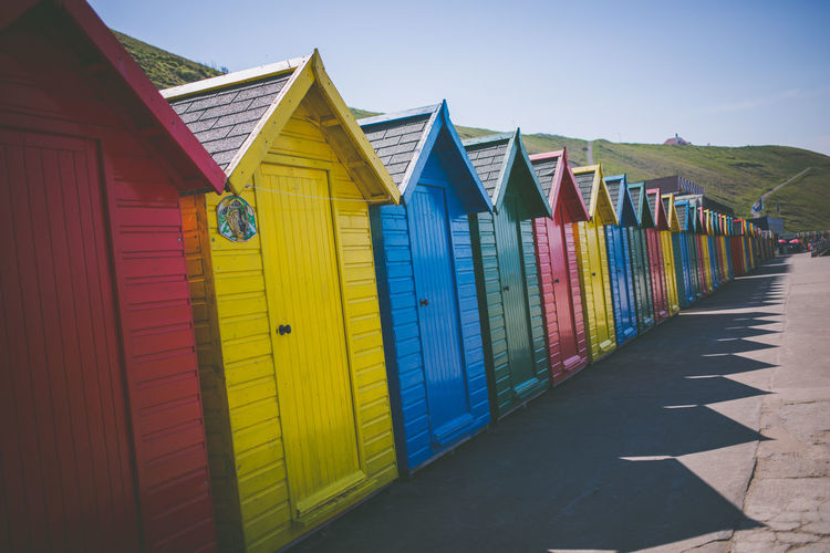 Whitby huts Whitby Architecture Beach Chalet Beach Hut Beach Huts Building Building Exterior Built Structure Clear Sky Day Direction House Hut In A Row Land Multi Colored Nature No People Outdoors Side By Side Sky The Way Forward Yellow