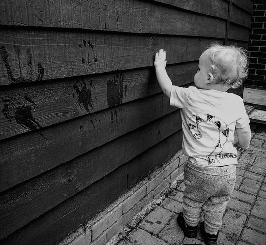 Rear view of baby boy standing by wooden wall