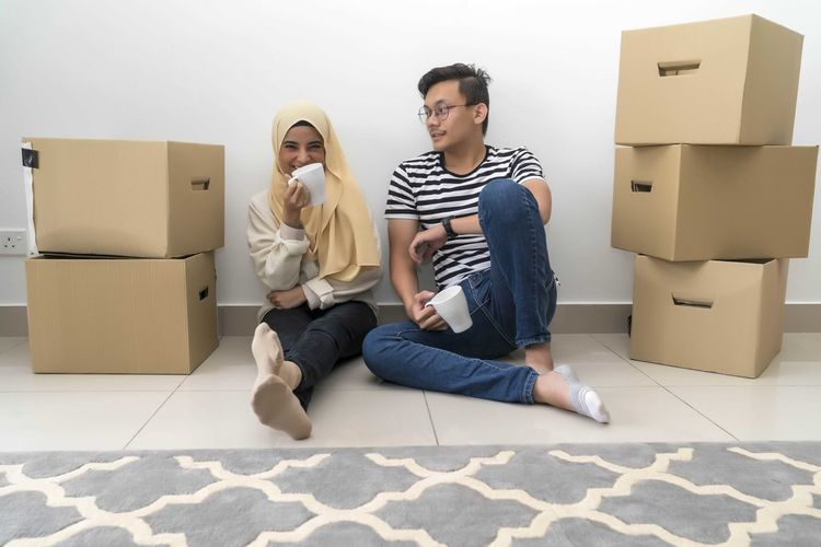 Young Malay Couple take a break after house moving Cardboard Box Cardboard Box Full Length Young Men Togetherness Young Adult Lifestyles Couple - Relationship Casual Clothing Indoors  Moving House Young Women Sitting Young Couple Men Heterosexual Couple Front View Two People Adult Flooring Boyfriend Change Packing Box - Container