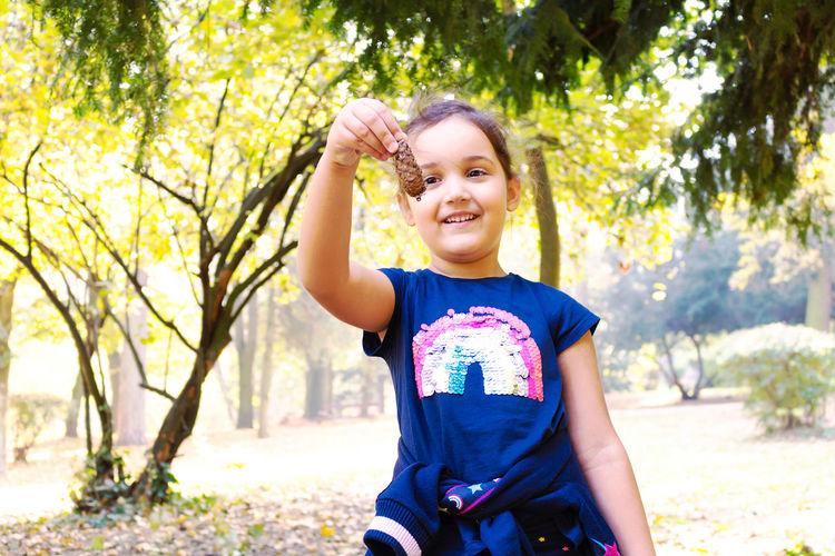 Portrait of smiling girl against trees