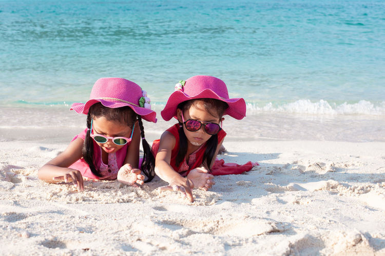 Girls playing with sand while lying at beach