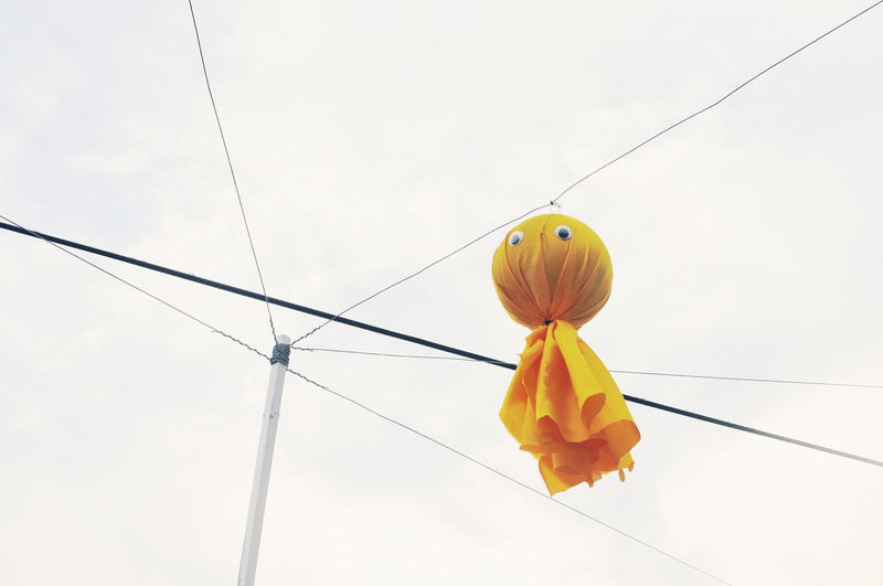 Low angle view of yellow decoration hanging from cable against sky