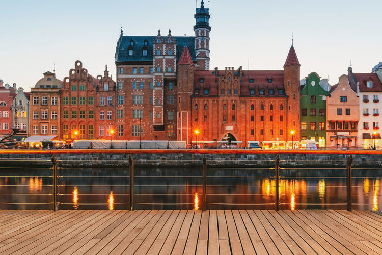 Facades of old medieval houses on the promenade in gdansk city. poland. wooden pier