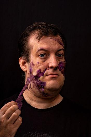 Portrait of man peeling of make-up against black background