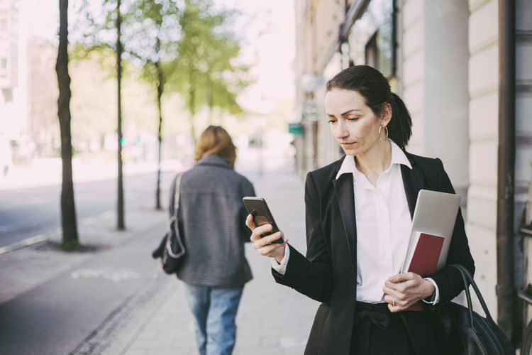 Woman holding mobile phone while standing on laptop