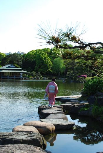 Rear view of woman in traditional clothing walking on stepping stones at park