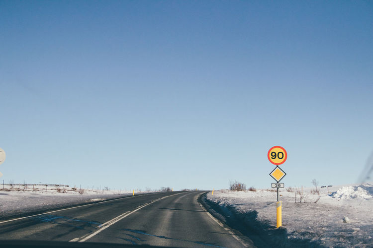 Road sign against clear sky