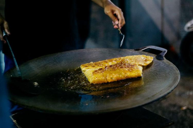 Cropped hands preparing food on pan