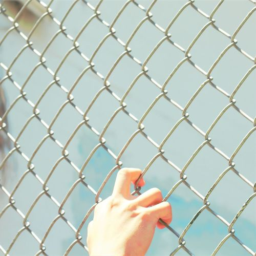 Close-Up Of Hand Clinging Onto Wire Metal Fence