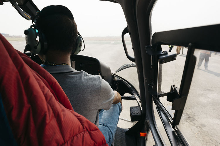 Rear View Of Man Sitting In Helicopter