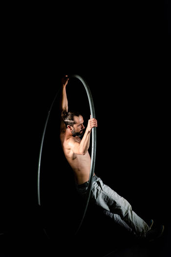 Circus Adult Arms Raised Black Background Copy Space Exercising Flexibility Front View Full Length Healthy Lifestyle Indoors  Mid Adult One Person Portrait Shirtless Sport Strength Studio Shot Young Adult