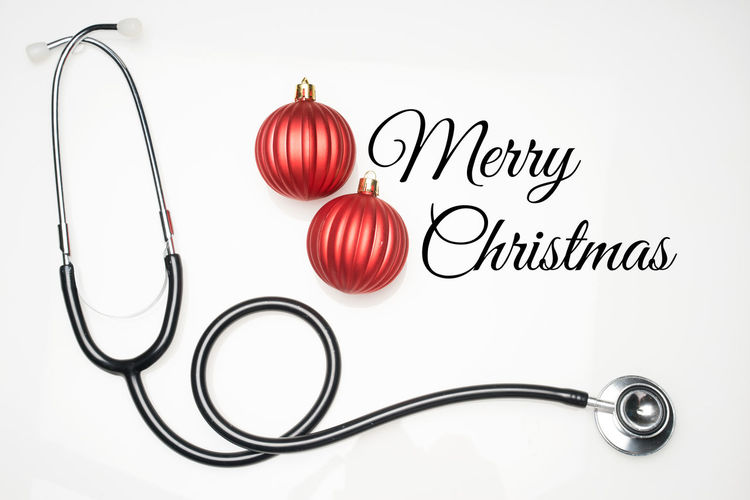 Christmas in the healthcare industry. Top view of flat lay. Stethoscope with ornaments carries an open interpretation of Christmas celebration in the medical world. Indoors  White Background Studio Shot Close-up No People Red Healthcare And Medicine Medical Stethoscope  Celebration Christmas Christmas Ornament Merry Christmas! Concept Decoration Hospital Oncall New Year Xmas Health Wish Season Greetings