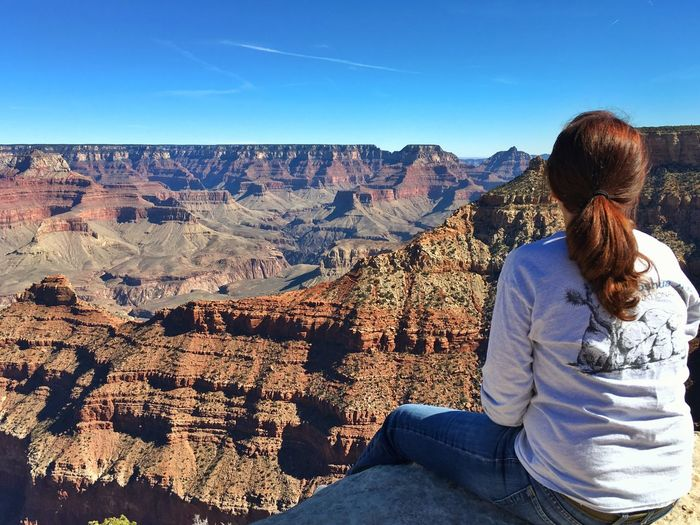 Rear View Of Looking At Grand Canyon National Park While Sitting On Cliff