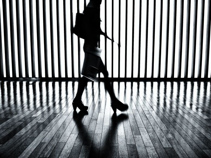 Low section of silhouette woman walking on hardwood flooring against metal fence