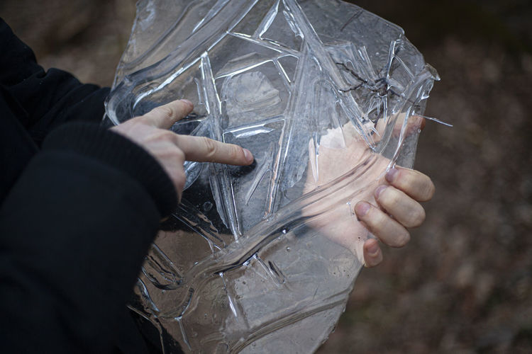 Close-up of hand holding ice outdoors