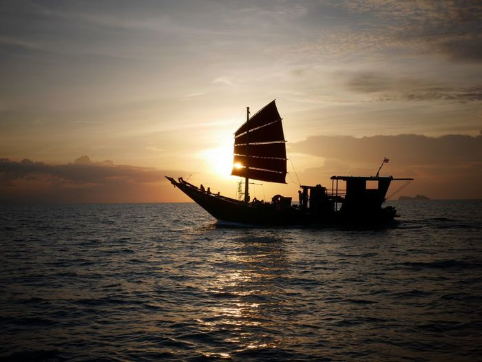 Silhouette ship sailing on sea against sky during sunset