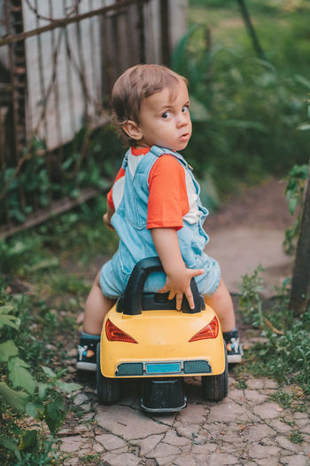 Portrait of cute boy sitting in toy car