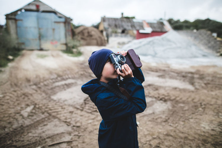 Boy photographing while standing on land