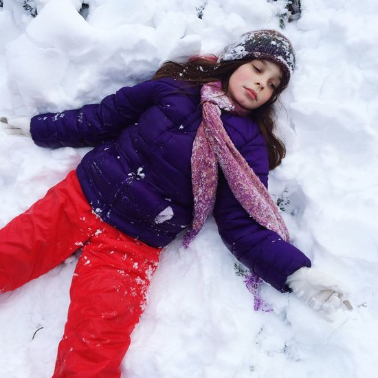 High Angle View Of Young Woman Lying On Snow