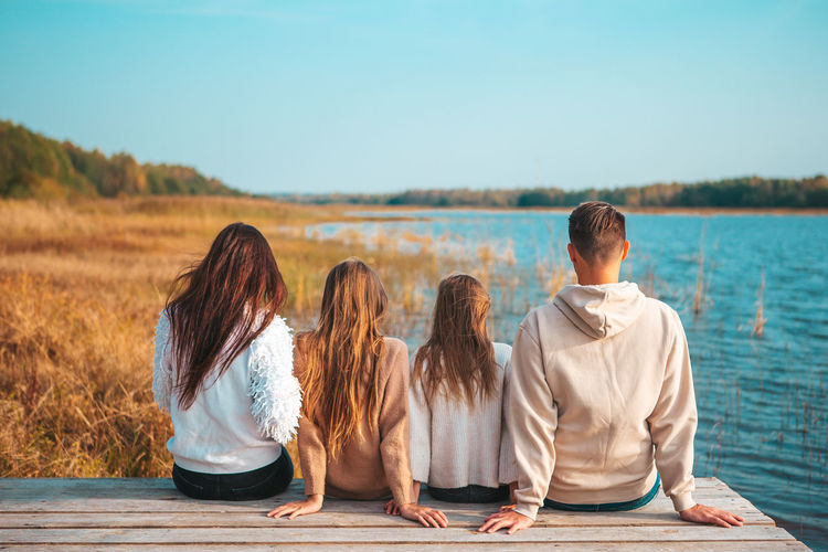 Rear view of friends sitting on shore against sky