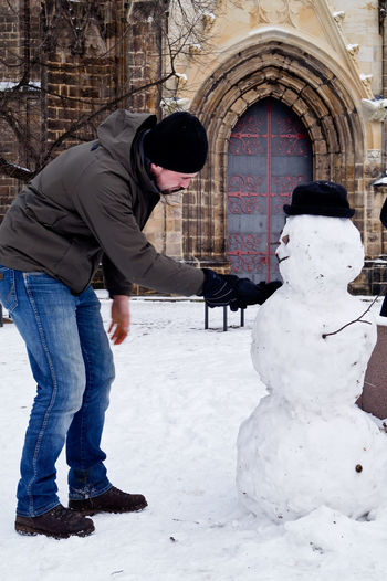 Man Touching Snowman While Standing Outdoors During Winter