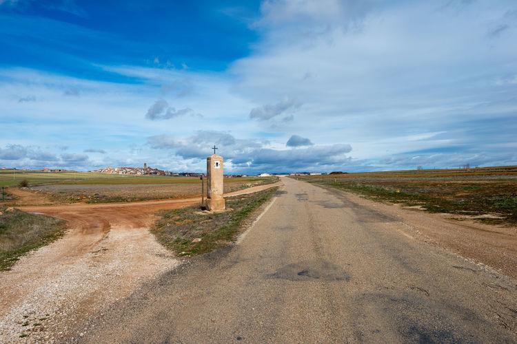 Dirt Road Along Landscape Against Sky