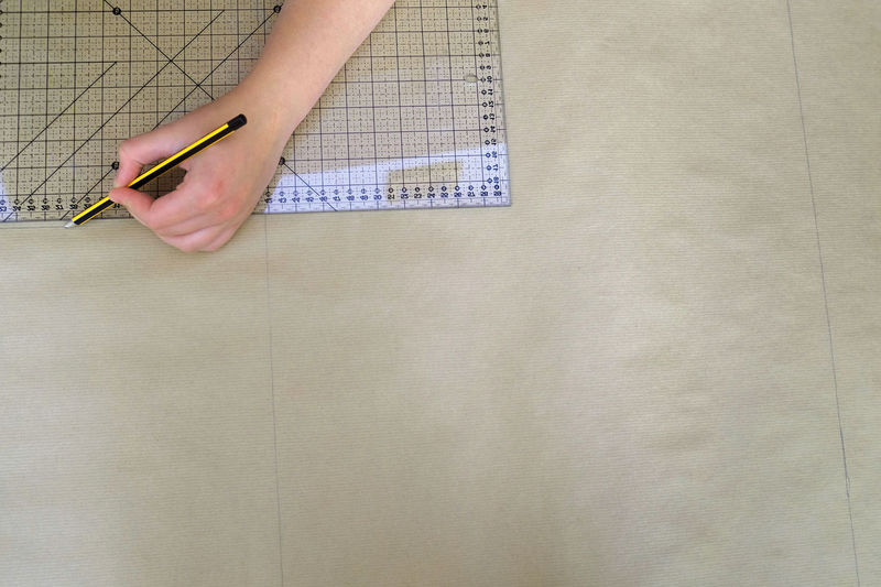 Cropped hands of woman drawing on paper at desk
