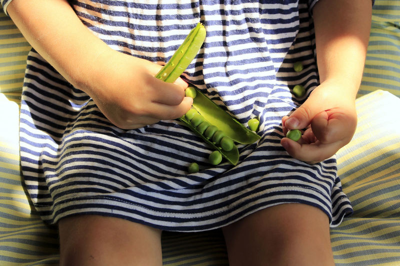 Midsection of girl holding green peas while sitting on bed at home
