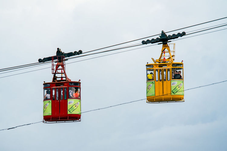 The bright red and yellow cars of the famous tourist attraction cables cars of Kutaisi, Georgia, about to pass each other mid ride. Architecture Built Structure Cable Cable Car Connection Construction Industry Crane - Construction Machinery Crossing Day Hanging Industry Low Angle View Machinery Mode Of Transportation Nature No People Outdoors Overhead Cable Car Passing Sky Transportation Travel