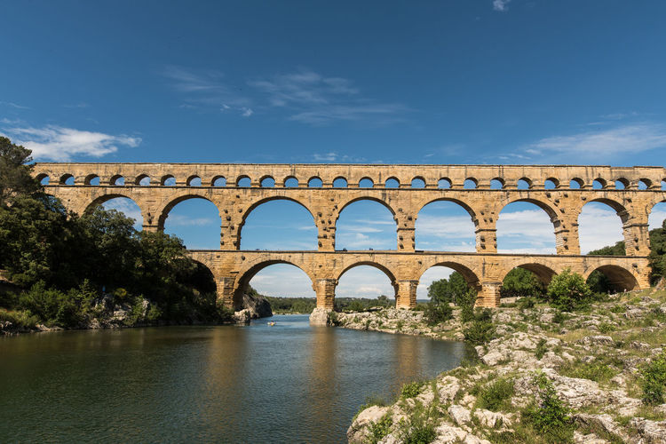 Ancient Aqueduct Arch Architecture Blue Bridge - Man Made Structure Built Structure Cloud - Sky Connection Day France Nature No People Old Ruin Outdoors Pont Du Gard Provence Provence-Alpes-Cote D'Azur Sky Travel Destinations Tree Viaduct Water