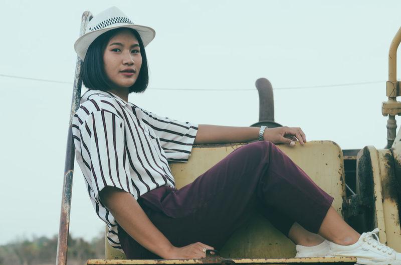 Portrait of smiling teenage girl in hat sitting against sky