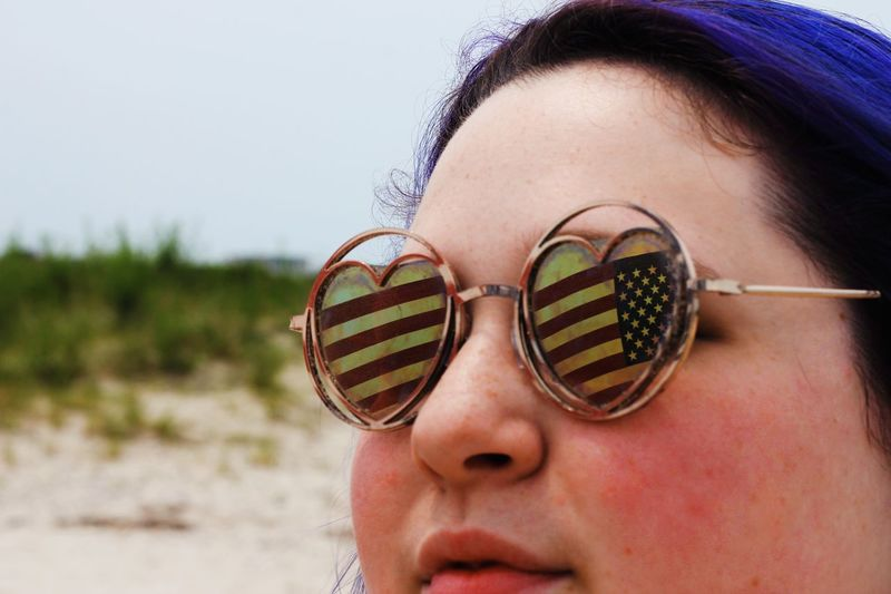 Fashionable woman with American flag in the heart shaped sunglasses 4th Of July EyeEm Selects Portrait One Person Headshot Real People Glasses Young Adult Young Women Leisure Activity Close-up Women Day Human Body Part Lifestyles Focus On Foreground Front View Body Part Human Face Outdoors