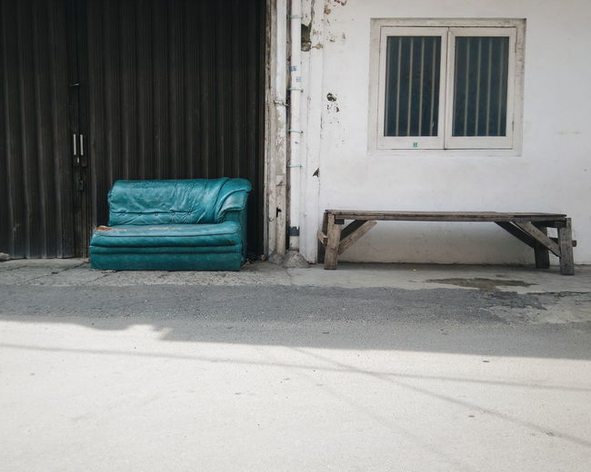 Old sofa by bench against building