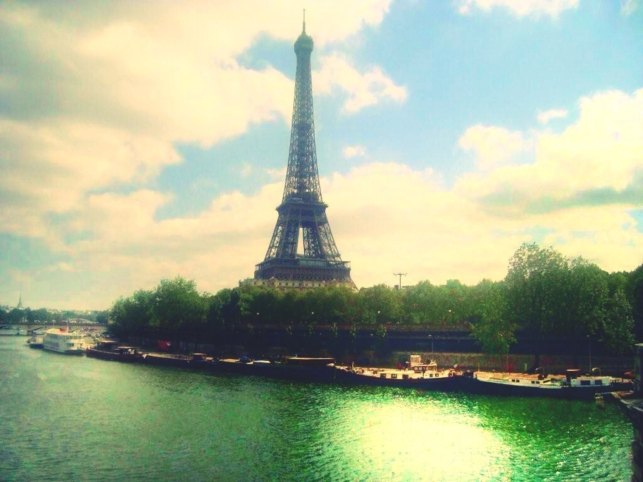 built structure, architecture, sky, water, famous place, eiffel tower, travel destinations, international landmark, tourism, tree, travel, tower, tall - high, cloud - sky, waterfront, capital cities, culture, building exterior, river, city