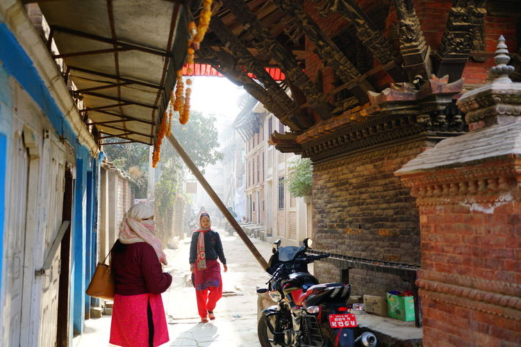 Rear view of women standing on street amidst buildings