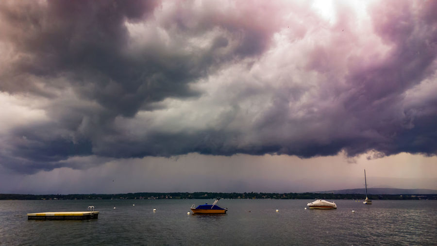 Sailboats sailing in sea against dramatic sky