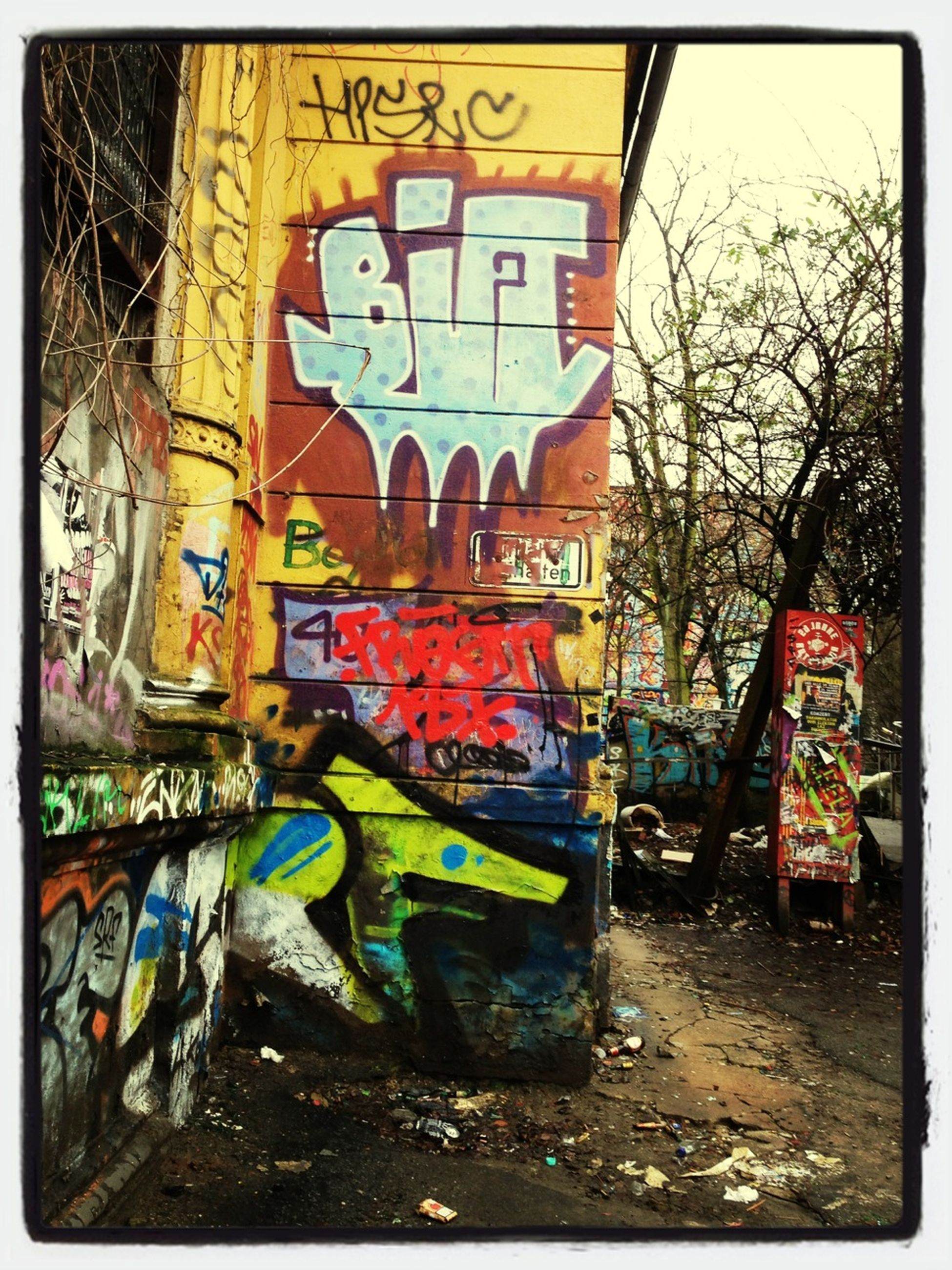 graffiti, transfer print, text, auto post production filter, built structure, architecture, western script, building exterior, transportation, wall - building feature, communication, art, art and craft, abandoned, creativity, mode of transport, day, old, tree, non-western script