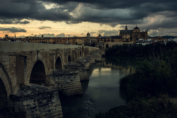 Bridge over river against buildings