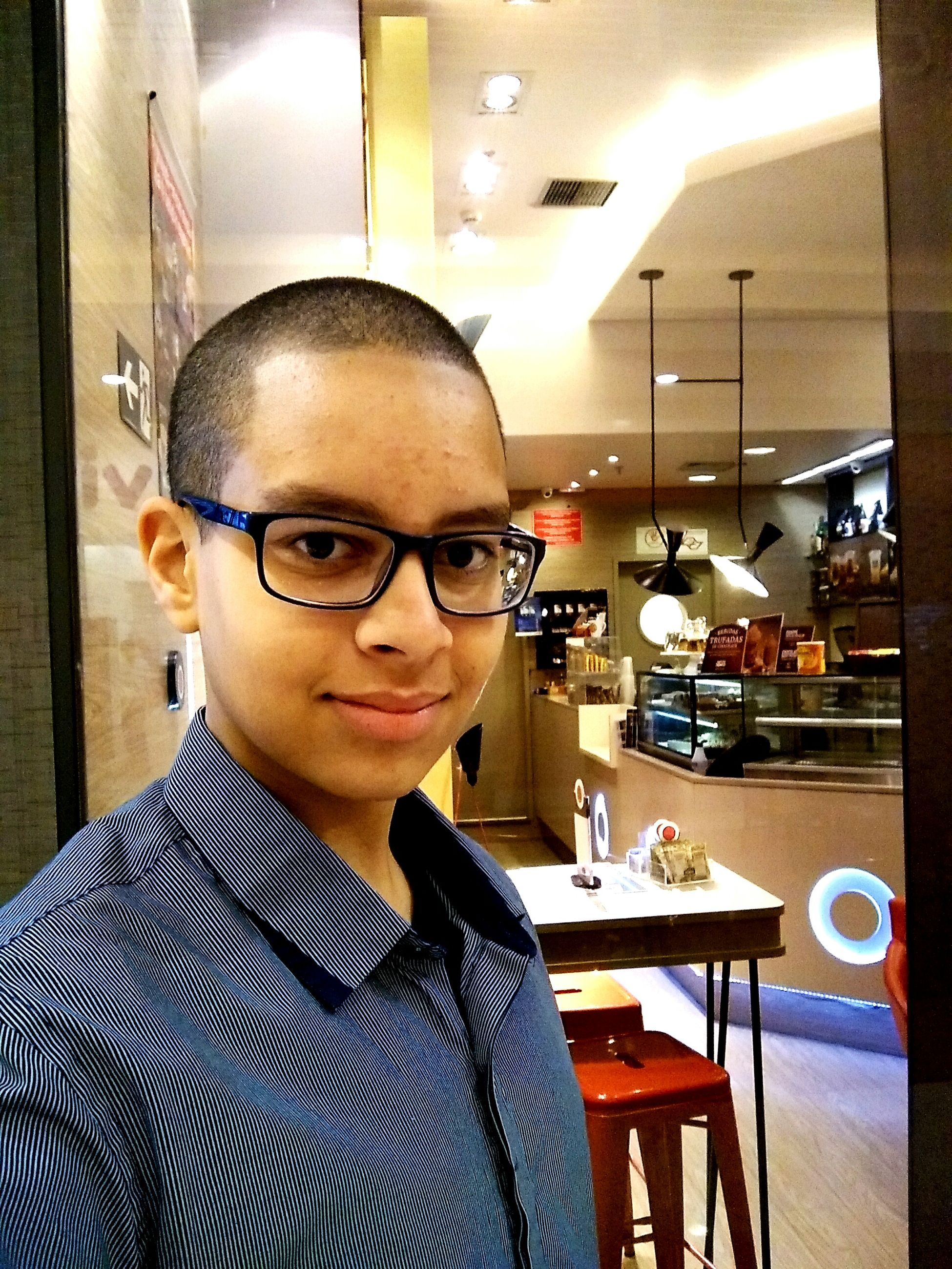 indoors, restaurant, real people, looking at camera, portrait, one person, young adult, front view, eyeglasses, table, cafe, lifestyles, headshot, sitting, illuminated, young women, day, close-up