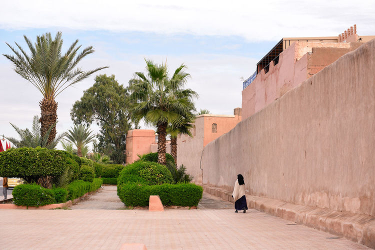 """A woman walking in a street in Marrakesh. It is the fourth largest city in the country, after Casablanca, Fez and Tangier. It is the capital city of the mid-southwestern region of Marrakesh-Safi. Located to the north of the foothills of the snow-capped Atlas Mountains, Marrakesh is situated 580 km (360 mi) southwest of Tangier, 327 km (203 mi) southwest of the Moroccan capital of Rabat, 239 km (149 mi) south of Casablanca, and 246 km (153 mi) northeast of Agadir. The ramparts of Marrakesh, which stretch for some 19 kilometres (12 mi) around the medina of the city, were built by the Almoravids in the 12th century as protective fortifications. The walls are made of a distinct orange-red clay and chalk, giving the city its nickname as the """"red city""""; they stand up to 19 feet (5.8 m) high and have 20 gates and 200 towers along them.[90] Bab Agnaou was built in the 12th century during the Almohad dynasty. The Berber name Agnaou, like Gnaoua, refers to people of Sub-Saharan African origin (cf. Akal-n-iguinawen – land of the black). The gate was called Bab al Kohl (the word kohl also meaning """"black"""") or Bab al Qsar (palace gate) in some historical sources. The corner-pieces are embellished with floral decorations. This ornamentation is framed by three panels marked with an inscription from the Quran in Maghrebi script using foliated Kufic letters, which were also used in Al-Andalus. Bab Agnaou was renovated and its opening reduced in size during the rule of sultan Mohammed ben Abdallah. Bab Aghmat is located east of the Jewish and Muslim cemeteries, and is near the tomb of Ali ibn Yusuf.[91] Bab Berrima with its solid towers stands near the Badi Palace. Bab er Robb (meaning """"Lord's gate"""") is a southern exit from the city, near Bab Agnaou. Built in the 12th century, it provides access to roads leading to the mountain towns of Amizmiz and Asni. Bab el Khémis, situated in the medina's northeastern corner, is one of the city's main gates and features a man-made spring. Marrake"""