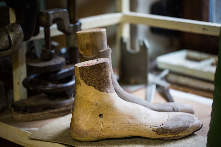 Close-Up Of Wooden Shoe Stretchers On Workbench At Workshop