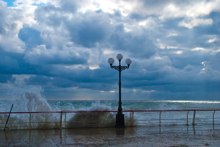 Street Light On Pier With Waves Splashing In Sea Against Cloudy Sky