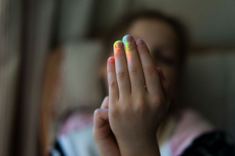 Close up of a girl's hand with rainbow coloured light reflected on fingers