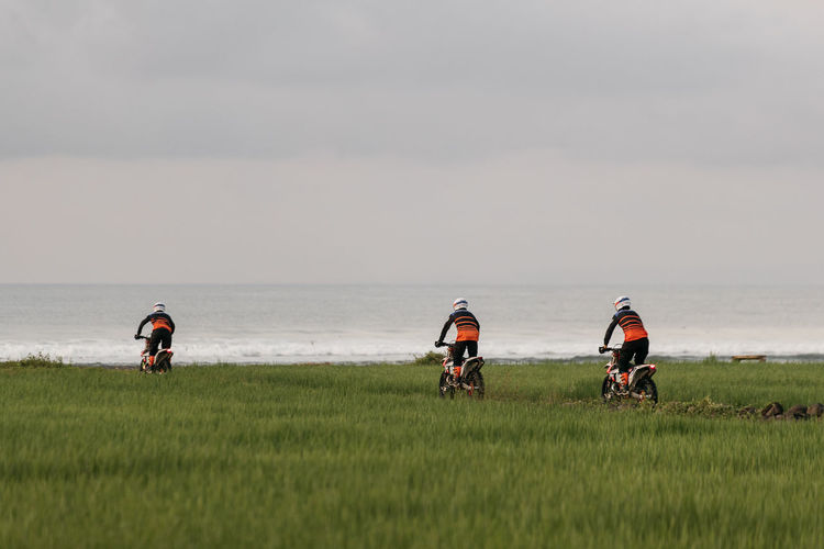 People riding dirt bikes on grass by sea against sky